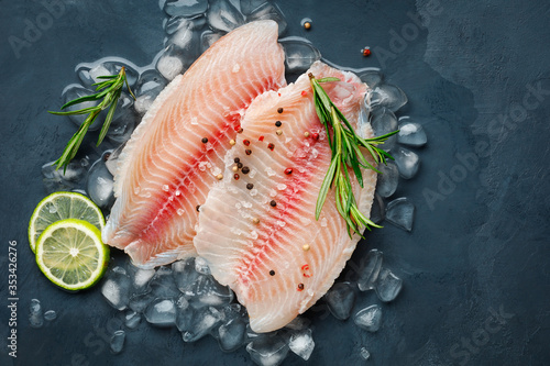 Fototapeta Fresh fish fillet of sea bass in ice on a dark slate background. Top view. obraz