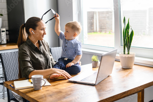 Cuadros en Lienzo Freelancer mom trying to work at home with a laptop, a toddler boy is snatching her eyeglasses