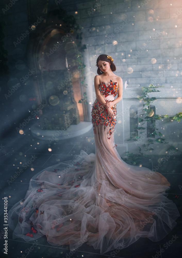 Fototapeta Fantasy beauty woman princess. glamorous peach creative dress long train. Fashion model posing in fairy room full magical divine light. Mystic art photo image of Queen Goddess Butterfly. Golden tiara