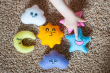 Baby Hand Pointing At A Handmade Felt Toy On The Beige Carpet. Educational Toys. Baby Acquaintance With Different Emotions And Feelings: Shyness, Love, Sadness, Sleepiness, Happiness, Joy.