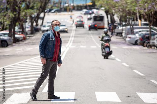 Fototapeta Uomo vestito casual con giacca in jeans e mascherina facciale protettiva , attraversa le strisce pedonali in pieno centro di una città obraz