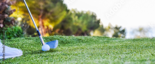 Fototapeta Golf clubs drivers over green field background