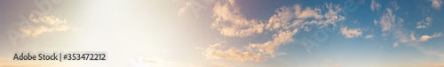 Obraz Warm sunny blue sky with fluffy clouds. Sunset sunlight illuminates the sky in sunset time. Beautiful ultra-wide panoramic background of atmosphere - fototapety do salonu