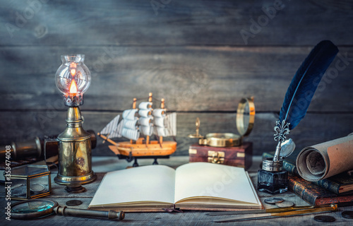 Fototapeta Travel and nautical theme grunge background. Old book, compass, telescope, divider, coins, shell, map, hourglass, quill pen on wood desk. Columbus Day. obraz
