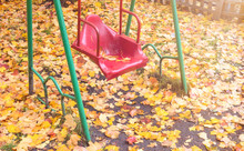 Autumn. Swings On The Playground After The Rain. The Ground Is Covered With Fallen Yellow And Red Leaves.