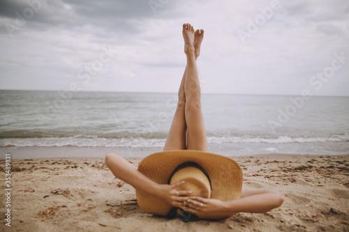 Valokuvatapetti Girl in hat lying on beach with legs up