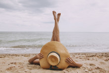 Girl In Hat Lying On Beach With Legs Up. Fashionable Young Woman Covering With Straw Hat, Relaxing On Sandy Beach Near Sea. Summer Vacation And Travel. Mindfulness And Carefree