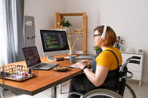 Obraz Smart disabled coder sitting in wheelchair and using computers while working from home - fototapety do salonu