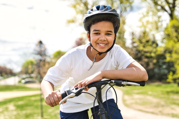 boy riding bike wearing a helmet outside