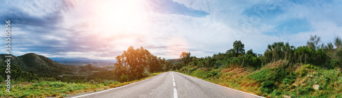 Obraz Empty long mountain road to the horizon on a sunny summer day at bright sunset - fototapety do salonu