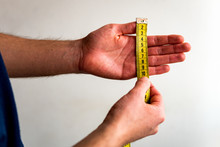 Person Transversely Measuring The Fingers Of His Left Hand From Thumb To Pinkie With A Yellow Tape Measure. White Background. Olive Skin Tone.