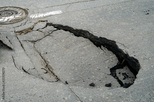 Fotomural huge pit hole on the road, failure in the asphalt, marked with a tire, dangerous