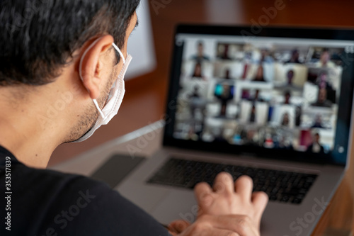 Man using a mask and having a video conference with work team amid COVID-19 pandemic Fotobehang