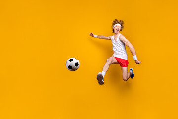Full length body size view of nice funky crazy overjoyed ecstatic glad excited cheerful cheery motivated guy jumping playing soccer isolated over bright vivid shine vibrant yellow color background