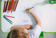 Portrait Of A Cute Little Girl Looking At The Camera And Smiling While Drawing Pictures Or Doing Homework, Sitting At A Table In The Home Interior, Copy Space