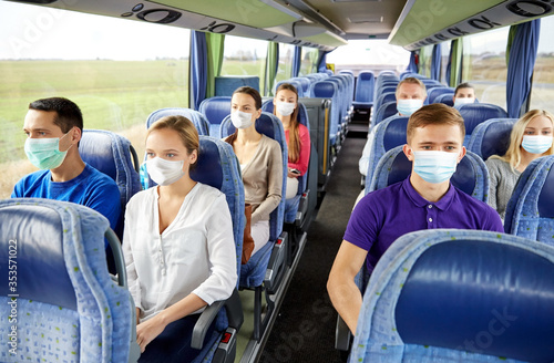 Obraz transport, tourism, road trip and people concept - group of passengers or tourists wearing face protective medical masks for protection from virus disease in travel bus - fototapety do salonu