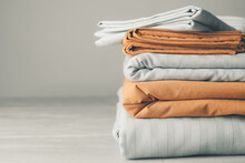Stack Of Clean Bed Sheets On Table