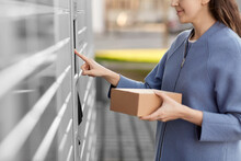 Mail Delivery And Post Service Concept - Close Up Of Happy Smiling Woman With Box At Outdoor Automated Parcel Machine Choosing Operation On Touch Screen