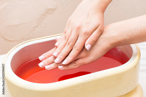 Fototapeta The process of paraffin therapy of a female hand is shot close up in a beauty salon