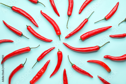 Leinwand Poster Hot chili pepper on color background