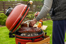 Red Ceramic Barbecue Grill. The Man Supervises The Grilling, Smoking, Baking, BBQ And Roasting Process.  Post-quarantine Picnic In  Homes Terrace.