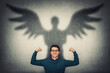 canvas print picture Confident businessman flexing muscles imagine superpower. Guy shows his strength, casting a superhero shadow with angel wings on a wall. Personal development, inner power and motivation concept.