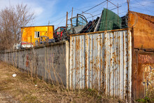 Rusty Fence With Barbed Wire In The Industrial Zone. Acceptance Of Black Scrap