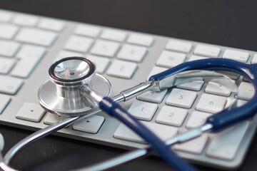 Silver stethoscope lying down on white keyboard, on black background. stock image photo. remote diagnostics