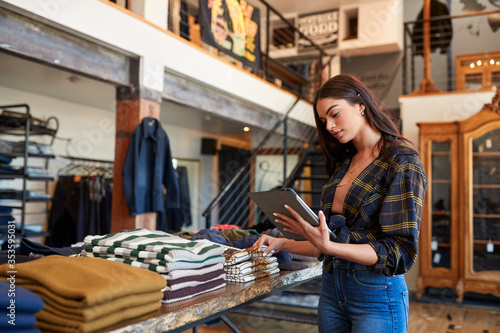 Fényképezés Female Owner Of Fashion Store Using Digital Tablet To Check Stock In Clothing St