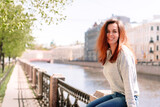 Fototapeta Londyn - A brunette girl is sitting on the embankment on a Sunny day, green trees everywhere, walking around the city