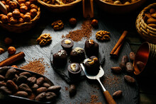 Six Chocolate Candies On Stand From Blackstone In Heart Shape With Cocoa Beans, Cinnamon, Nuts, Cocoa Powder Around