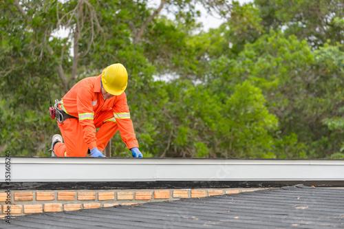 Fotografia, Obraz Construction worker putting the asphalt roofing (shingles) with nail gun on a la