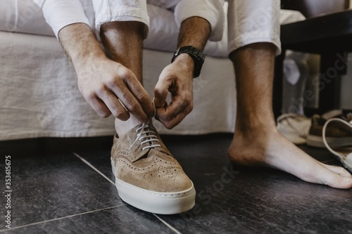 Fotografía Horizontal shot of a man tying shoelaces of brown shoes