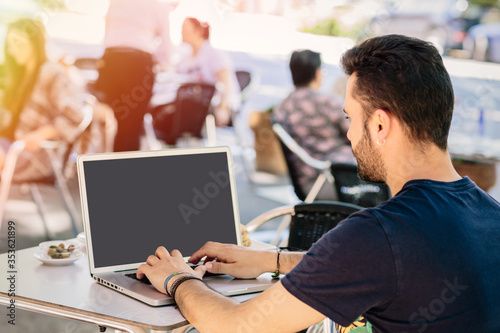 detail of the hands of a young boy working with his laptop from the outside terrace of a bar in Spain Fototapete