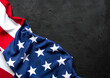 Flag of the United States freely lying on concrete black background with copy space