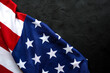 Top view of American Flag on black dark concrete background with copy space.