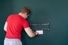 Repair And Decoration. 'husband For An Hour' Service. A Man Attaches A TV Mount To A Wall.