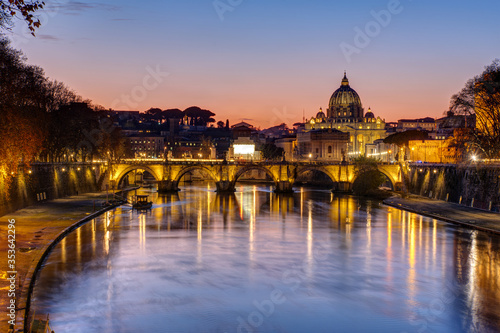 Leinwand Poster Sunset over the St. Peters Basilica and the river Tiber in Rome