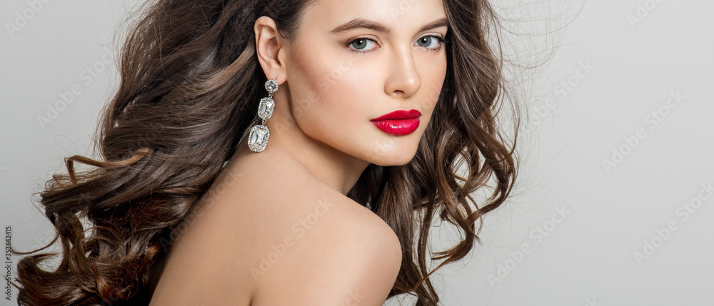 Fototapeta Beautiful girl with long wavy hair. Brunette with curly hairstyle. Professional Makeup. Fashion Earrings.
