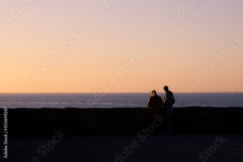 A young man and a woman looks out over the ocean during sunset in Malmö, Sweden Wallpaper Mural