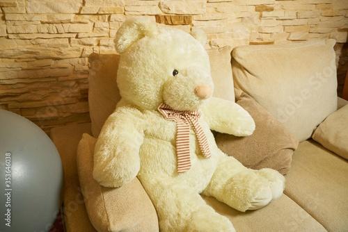 Closeup shot of a big toy bear put on a sofa