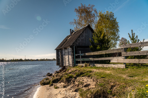 Vászonkép A picturesque fishing house with a washed-out Foundation on the Bank of the Volkhov river at the exit to lake Ladoga