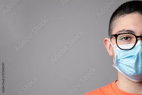 Fotografering Ritratto stretto di un Ragazzo giovane con mascherina , isolato su sfondo grigio