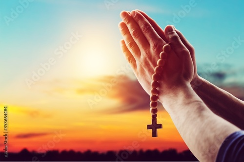Leinwand Poster Human male hand with the rosary and cross