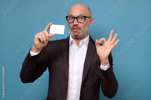 Handsome bald business man with beard holding credit card over isolated blue bac Wallpaper Mural