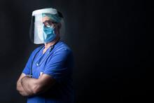Medico In Camice Blu , Cuffietta Verde,  Visiera Protettiva Indossa Una Mascherina Chirurgica Incrocia Le Braccia Isolato Su Sfondo Nero