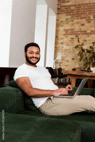 Obraz cheerful african american freelancer sitting on sofa with laptop and looking at camera - fototapety do salonu
