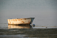 A Small Old Boat Anchored At S...