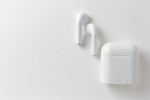 Modern Wireless Earphones And Charging Case On White Background, Flat Lay