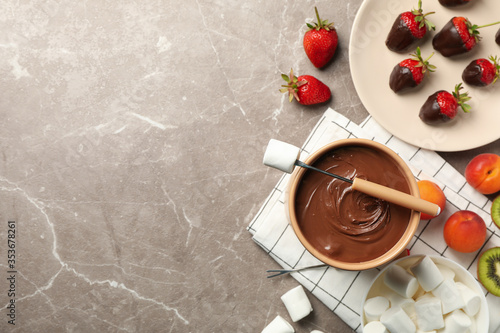 Fototapeta Composition with ingredients for chocolate fondue on gray table. Cooking fondue obraz